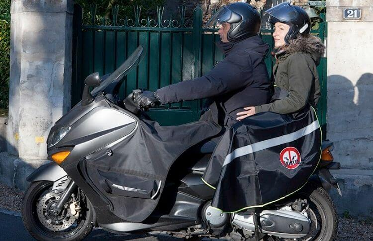 Un couple sur un scooter avec le passager protégé par un tablier
