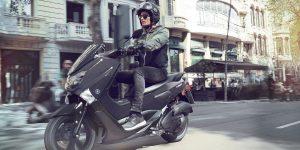 Un homme conduit un scooter en ville - comment choisir son assurance scooter ?