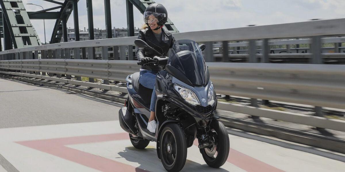 Une conductrice sur un scooter 3 roues - Les différentes formules en assurance scooter