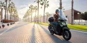 Un scooter sur une route ensoleillée avec un conducteur souriant