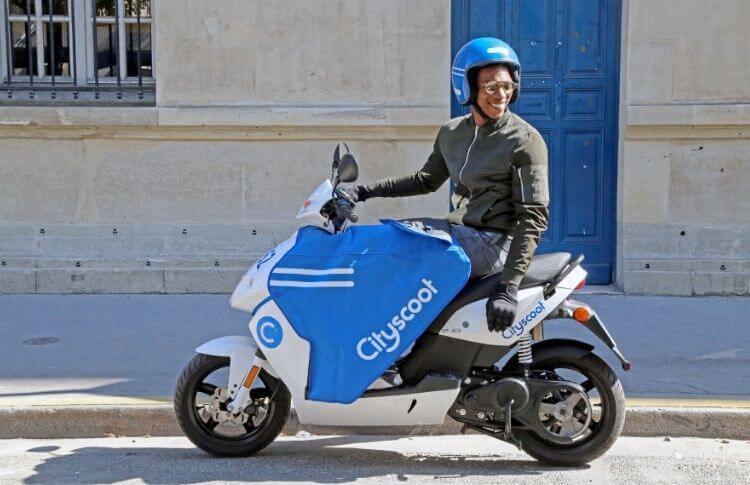 Un jeune conducteur sur un scooter électrique Cityscoot
