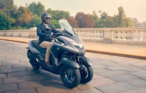 Un homme sur un scooter 3 roues sur un pont