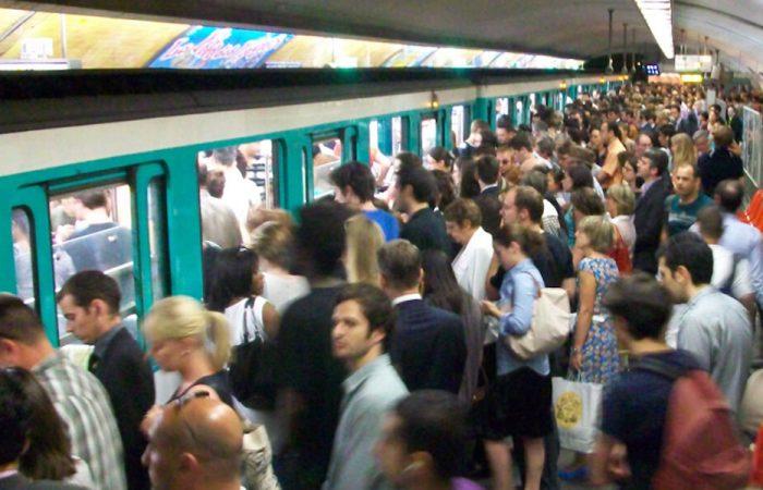 Des voyageurs sur le quai d'une station de métro parisienne qui monte dans les wagons