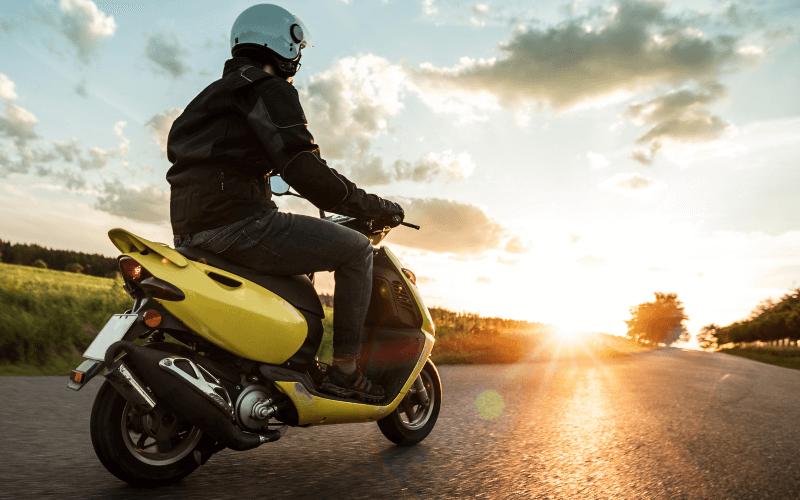 Un scooter circule sur une route de campagne